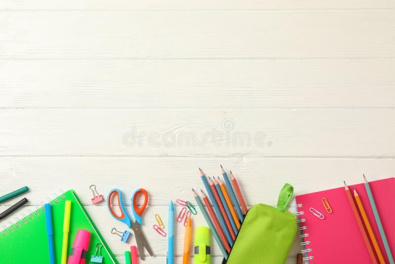 Flache gelegte Zusammensetzung mit Schulbedarf auf weißem hölzernem Hintergrund lizenzfreies stockfoto