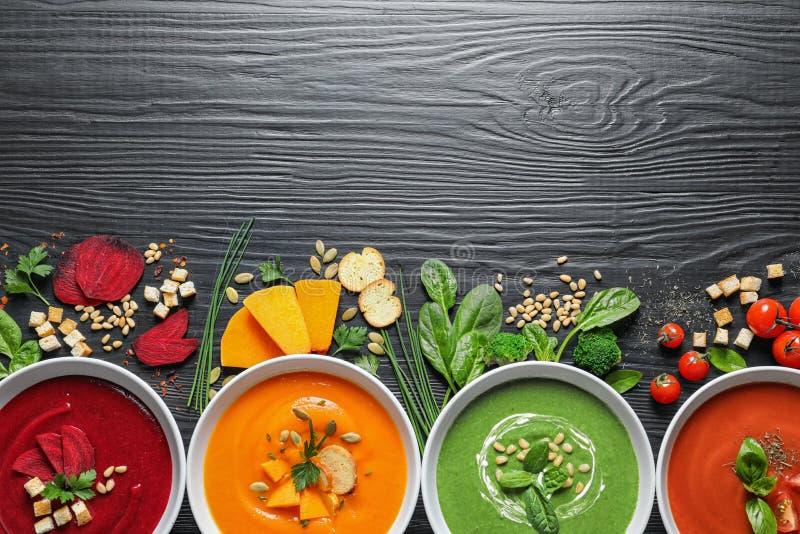 Flache gelegte Zusammensetzung mit verschiedenen Suppen, Bestandteilen und Raum für Text auf hölzernem Hintergrund stockbilder