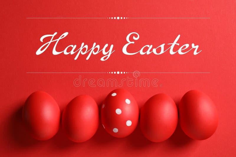 Flache gelegte Zusammensetzung von roten gemalten Eiern und von Text fröhliche Ostern lizenzfreie stockfotos