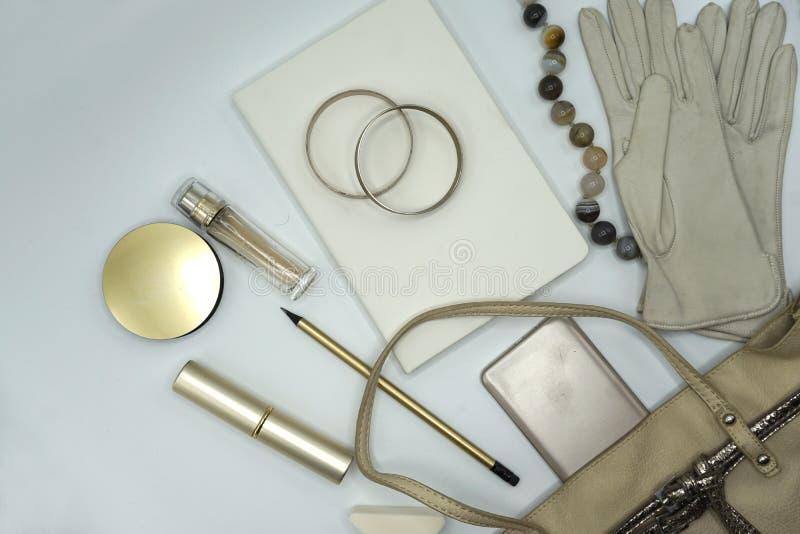 Flache gelegte Zusammensetzung von Schönheitsprodukten und Handtasche für Frauen Pastell- und Goldfarben auf weißem Hintergrund lizenzfreies stockbild