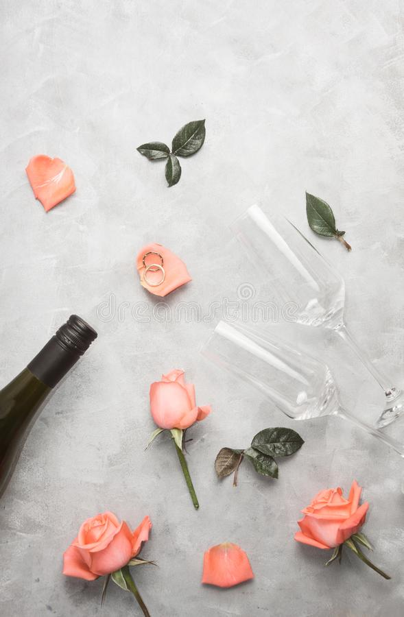 Flache goldene Eheringe der Draufsicht der Lage mit Rosen und Champagnergläsern auf grauem konkretem Hintergrund lizenzfreies stockbild
