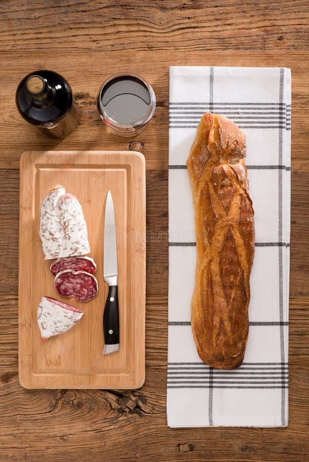 Flache Lage über Ansicht von Dauerwurstdelikatessen schnitt Fleisch mit Wein und traditionellem Brot auf hölzernem Brett stockbild