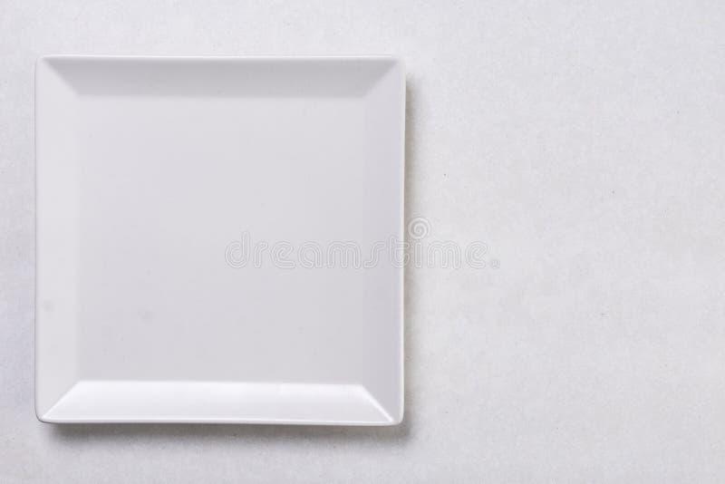 Flache Lage über Platte des weißen Quadrats auf der weißen Marmorhintergrundtabelle lizenzfreie stockfotografie