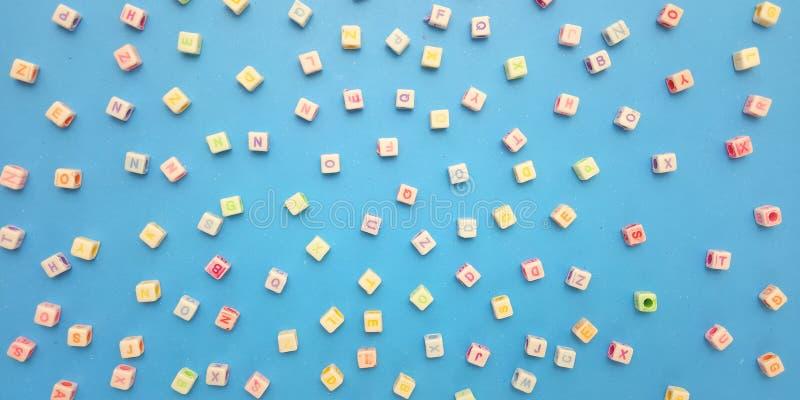 Flache Lage, blauer Hintergrund und Alphabet-Plastikw?rfel-Perlen-Element-Entwurfs-und Blasen-Schw?tzchen f?r Mitteilung, Zitat,  lizenzfreies stockfoto