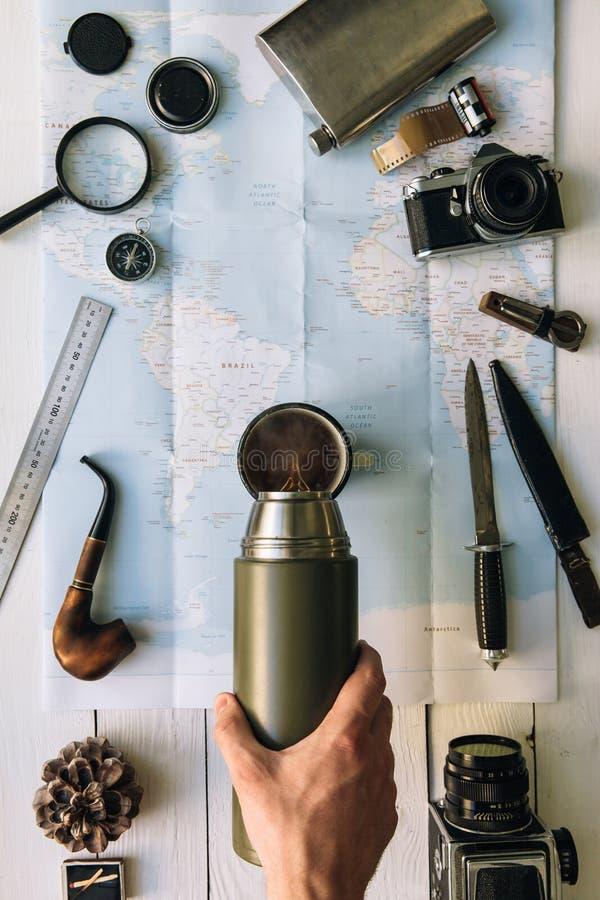 Flache Lage der Abenteuerplanung Reiseweinlesegang auf Karte Reisender, Forscherhände in auslaufendem Kaffee des Rahmens oder Tee stockbild