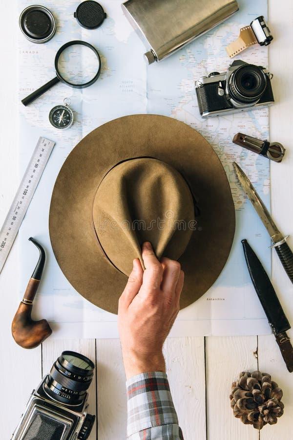 Flache Lage der Abenteuerplanung Reiseweinlesegang auf Karte Reisender, Forscherhände im Rahmen, der Hut nimmt oder setzt Erforsc lizenzfreie stockbilder