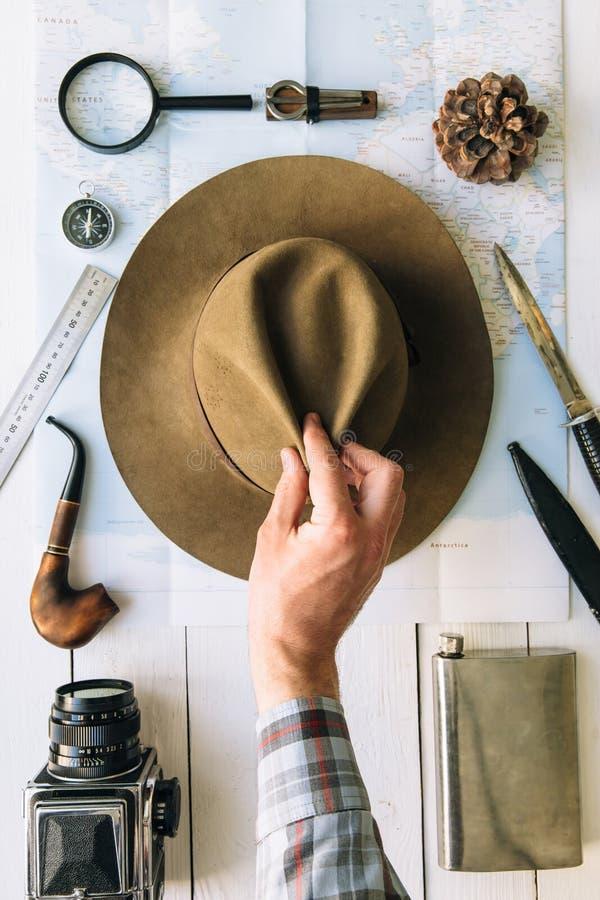 Flache Lage der Abenteuerplanung Reiseweinlesegang auf Karte Reisender, Forscherhände im Rahmen, der Hut nimmt oder setzt Erforsc stockfotos