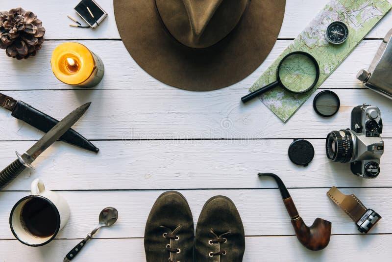 Flache Lage der Abenteuerplanung Reiseweinlesegang auf weißem Holztisch Einschließlich Filmkamera Hut, Messer, Vergrößerungsglas, stockfotos