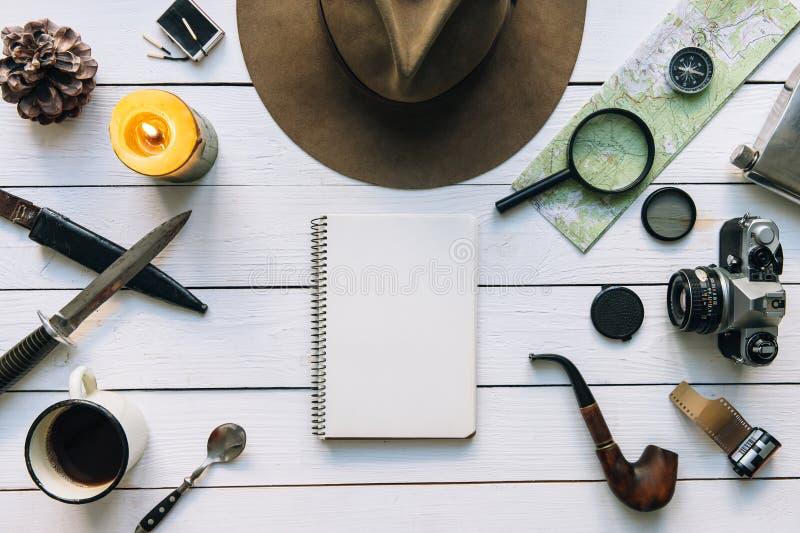 Flache Lage der Abenteuerplanung Reiseweinlesegang auf weißem Holztisch Einschließlich Stiefel Pfeife, Hut, Notizblock Erforschun lizenzfreie stockfotografie