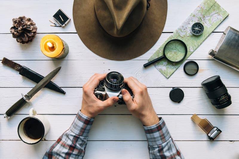 Flache Lage der Abenteuerplanung Reiseweinlesegang auf weißem Holztisch Mannhände in der Rahmenholdingweinlese-Filmkamera erforsc lizenzfreies stockbild