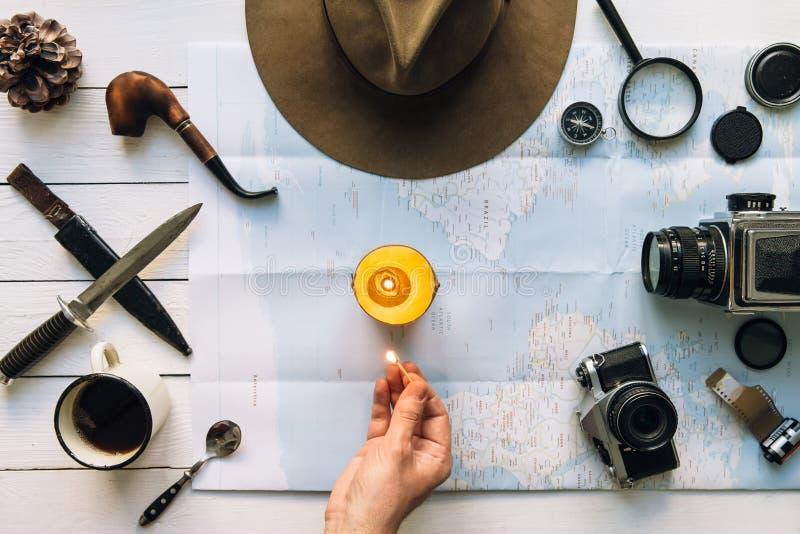 Flache Lage der Abenteuerplanung Reiseweinlesegang auf weißem Holztisch Mannhand in der Rahmenbeleuchtungskerze Erforschung, wand stockfotografie