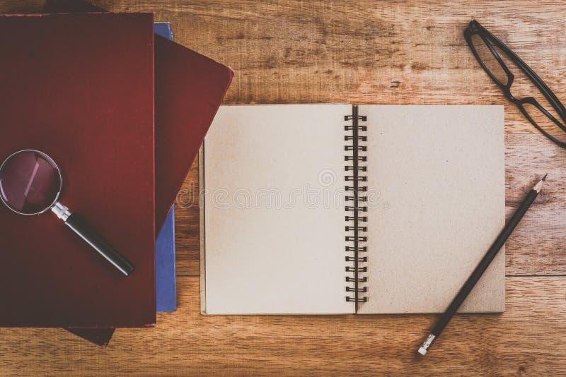 Flache Lage der Bildung mit alten Büchern, Bleistift, Gläsern und Lupe stockfoto