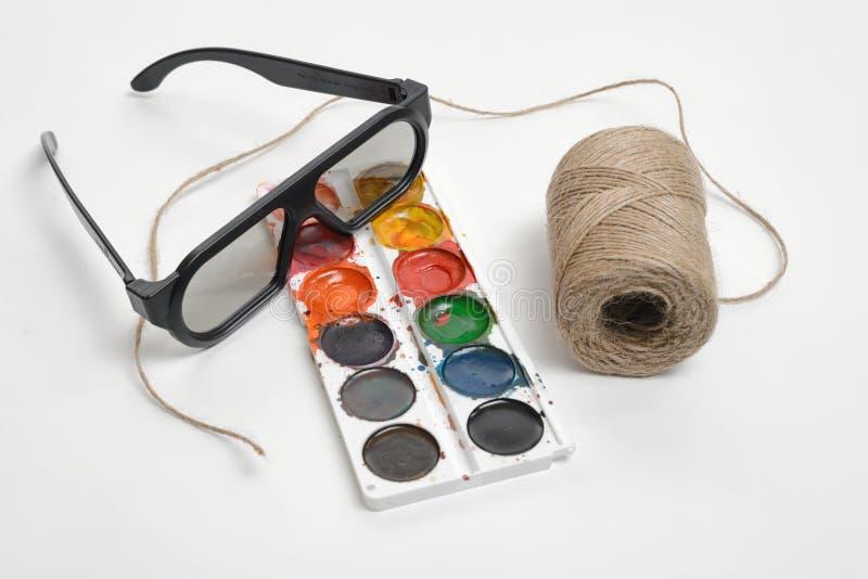 Flache Lage der Kunstszene Threadschnur, Gläser und Aquarellfarben auf einem weißen Hintergrund kennzeichnend lizenzfreie stockfotografie