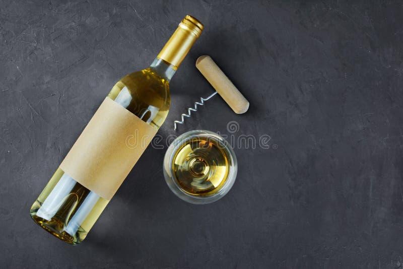 Flache Lage der Lügenweißweinflasche mit leerem Aufkleber, Korkenzieher und Glas für das Schmecken stockbilder