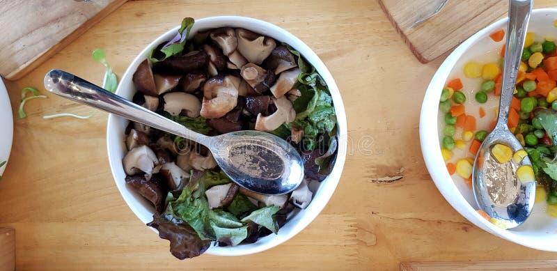 Flache Lage der Schüssel des Pilzes mit geschnittener grüner Bohne, Karotte und Mais mit Edelstahllöffel auf Holztisch lizenzfreie stockbilder