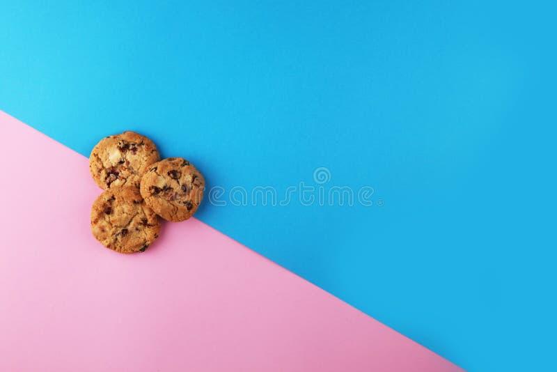 Flache Lage der Schokoladenplätzchen auf farbigem Papier stockfotografie