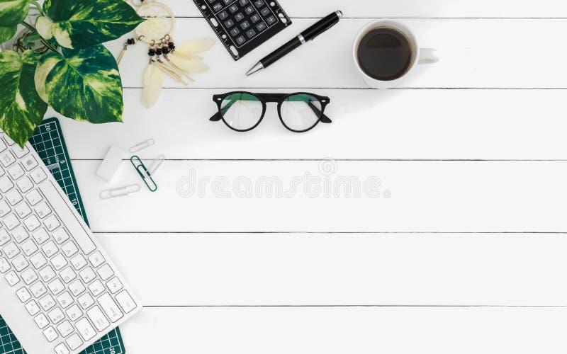 Flache Lage der Schreibtischarbeitsplatztabelle mit drahtloser Tastatur des Computers und stationär im Innenministerium auf weiße lizenzfreies stockbild