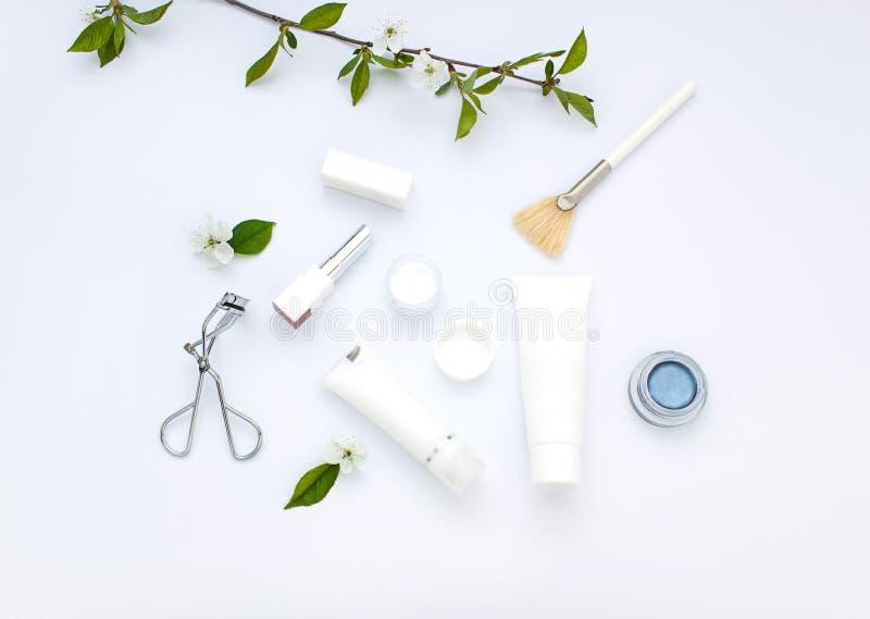 Flache Lage der weißen Kosmetik mit Blumen und Blättern Säubern Sie Schönheitskonzept stockfoto