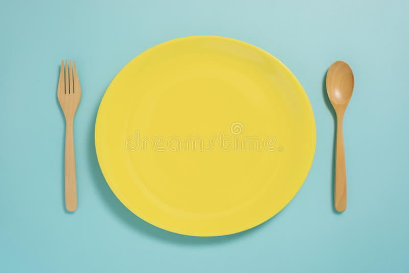 Flache Lage des Geschirrs, der gelben Platte und der Gabel auf blauem Pastellcolo stockfotografie