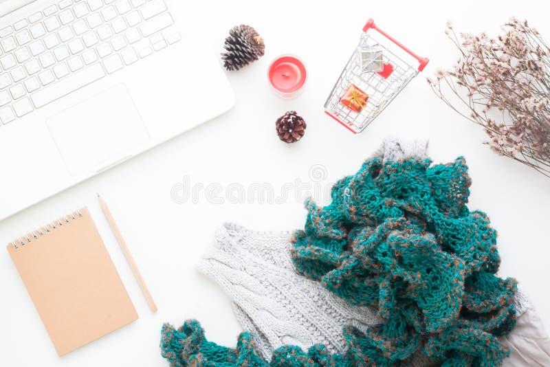 Flache Lage des kreativen Arbeitsplatzes mit Laptop, Warenkorb, Geschenkboxen und Winterkleidung auf Weiß stockfotografie