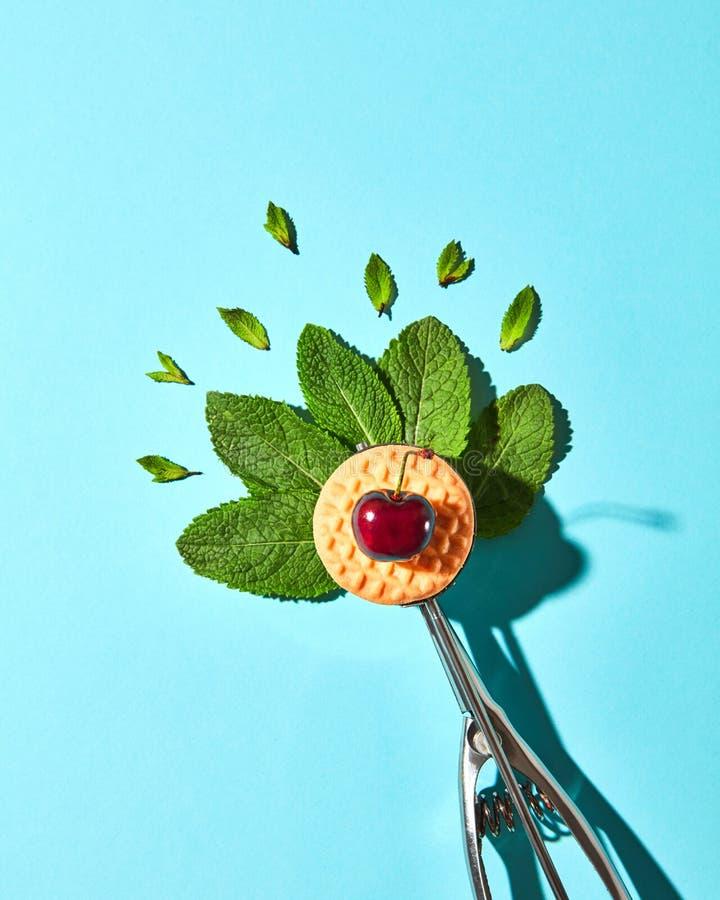 Flache Lage des Löffels für Eiscreme mit tadellosen Blättern, Keks und Kirsche auf einem blauen Hintergrund mit harten Schatten N lizenzfreie stockfotos