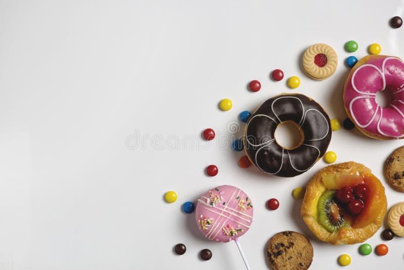 Flache Lage des Nachtischs mit Süßigkeit, Schokolade und Erdbeerschaumgummiringe und -fruchtkuchen lizenzfreie stockbilder