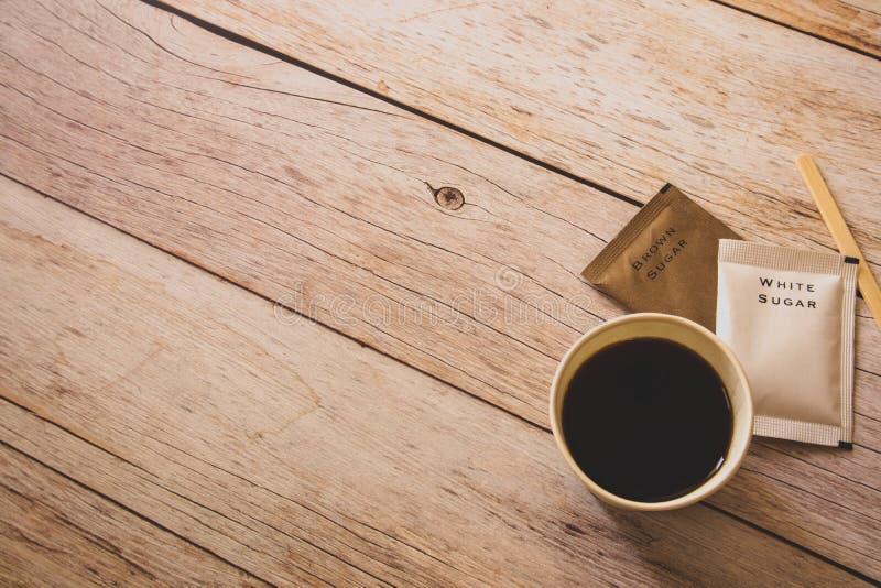 Flache Lage des schwarzen Kaffees in der Weißbuchschale mit weißer und brauner Zuckertaschen und hölzernem Stock auf Holztisch al lizenzfreies stockfoto