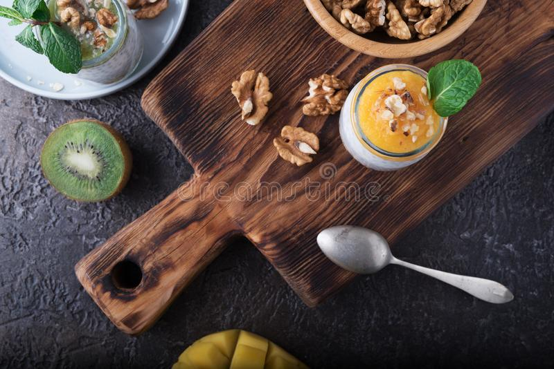Flache Lage des selbst gemachten Puddings von Chia-Samen und von Mandelmilch mit Getreide und Püree der Kiwi und der Mango mit Wa lizenzfreies stockfoto