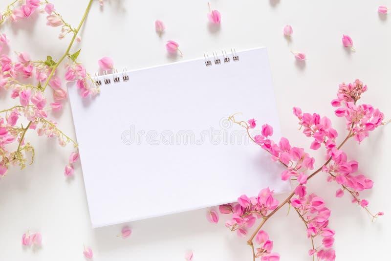 Flache Lage des weißen leeren Kalenders mit Kopienraum verzieren mit der rosa Blume, die auf weißem Hintergrund lokalisiert wird stockbilder