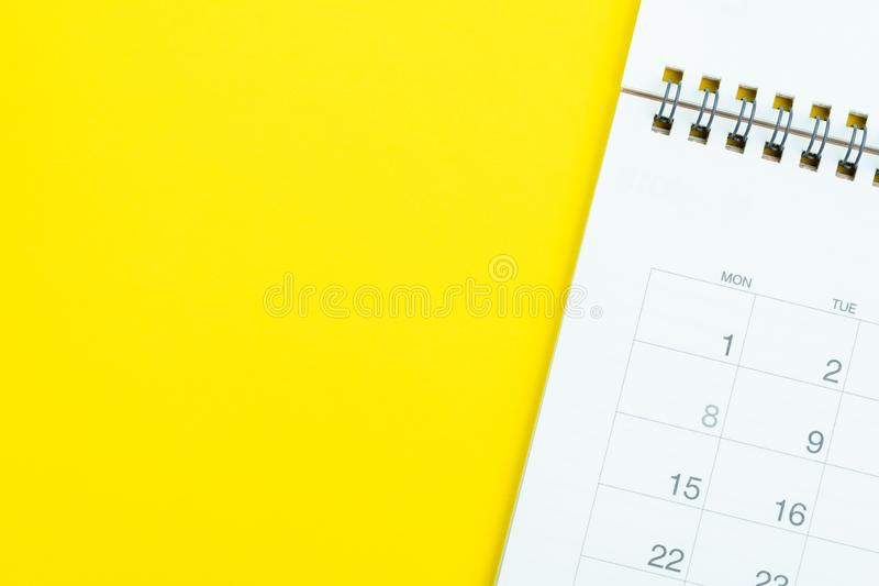 Flache Lage des weißen sauberen Tischplattenkalenders auf festem gelbem Hintergrund mit als Anzeige, Notiz, Sitzung oder Projekt  lizenzfreie stockbilder