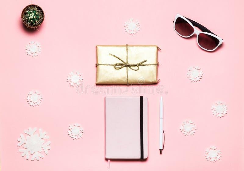 Flache Lage, Draufsicht Weihnachtswinter verzierte Tabelle Weiblicher Schreibtischarbeitsplatz mit Schneeflocken, rosa Notizbuch, lizenzfreies stockbild