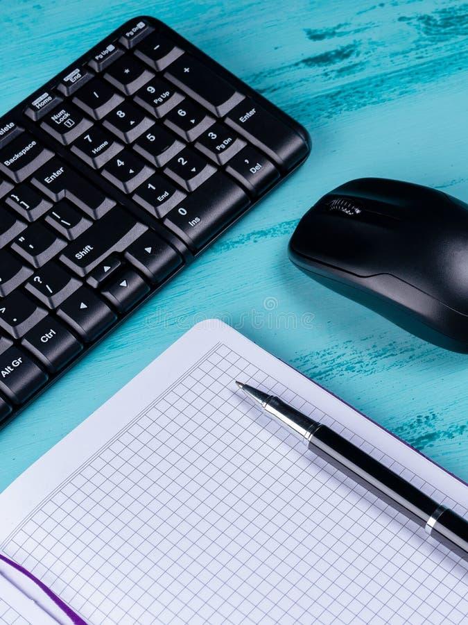 Flache Lage, Draufsichtbürotischschreibtisch Arbeitsplatz mit leerem Anmerkungsbuch, Tastatur, Büroartikel, auf hölzernem Hinterg lizenzfreie stockfotos