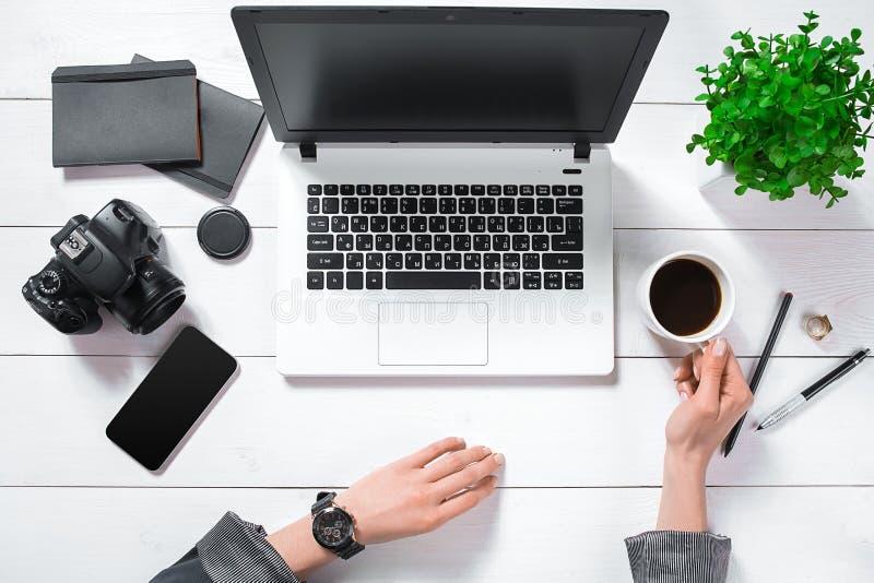 Flache Lage, Draufsichtbürotischschreibtisch Arbeitsplatz mit Mädchen ` s Händen, Laptop, grüne Blume in einem Topf, schwarzes Ta stockfotografie