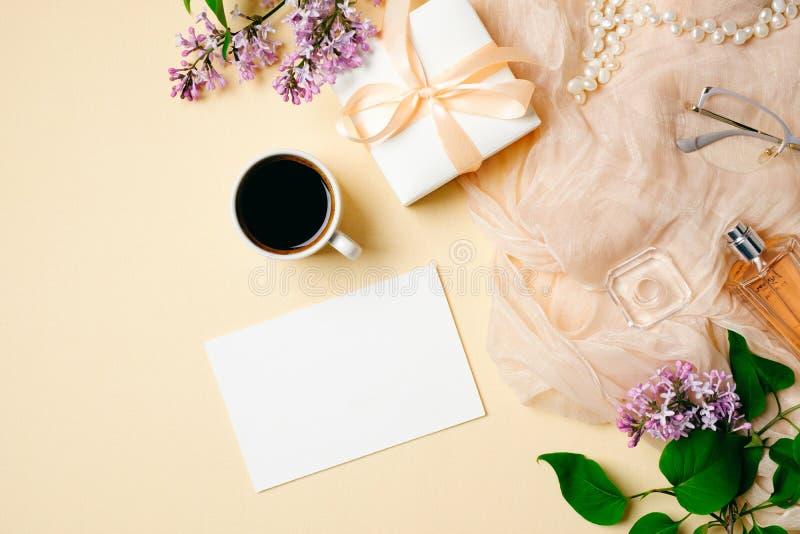 Flache Lage, Draufsichtb?rotischschreibtisch Frauenarbeitsplatz mit Papierkarte, Kaffeetasse, lila Blumenblumenstrauß, Geschenkbo stockbild