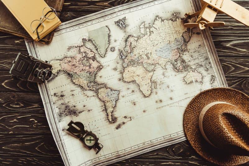 flache Lage mit Strohhut, Karte, hölzerner Spielzeugfläche, Kompass und Retro- Fotokamera auf Dunkelheit lizenzfreie stockbilder