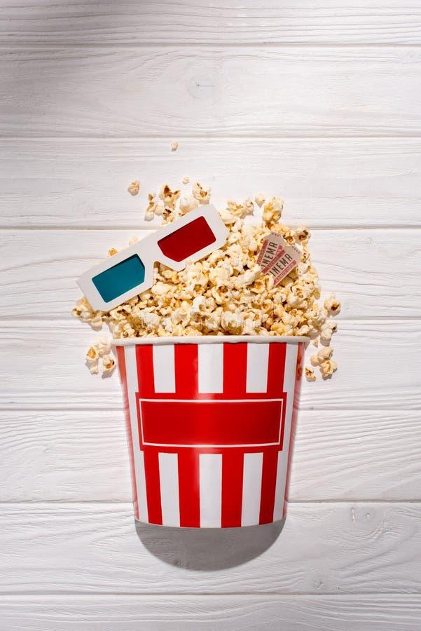 flache Lage mit Wegwerfeimer mit Popcorn, Retro- Kinokarten und Gläsern 3d auf weißer Holzoberfläche lizenzfreie stockbilder
