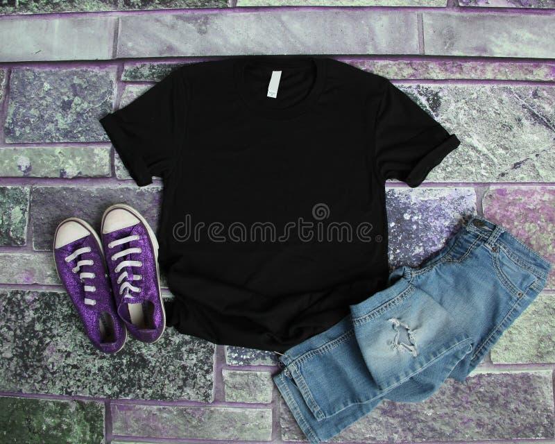 Flache Lage schwarzen T-Shirt Modells auf purpurrotem Ziegelsteinhintergrund mit PU lizenzfreie stockfotos