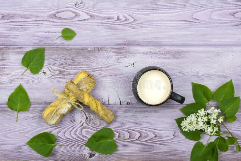 Flache Lage Schwarzer Becher mit Milch Selbst gemachte süße Plätzchen Zweig und weiße lila Blumen auf dem Tisch lizenzfreie stockbilder