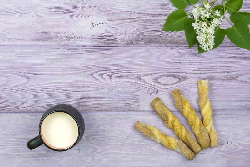 Flache Lage Schwarzer Becher mit Milch Selbst gemachte süße Plätzchen Zweig und weiße lila Blumen auf dem Tisch stockfoto