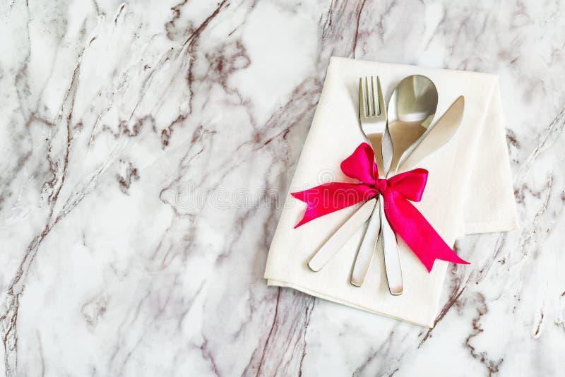 Flache Lage - Tischbesteck, L?ffelgabel und Messer auf einer rustikalen Serviette und ein Bogen von der Seidenbandl?ge auf einer  stockfoto
