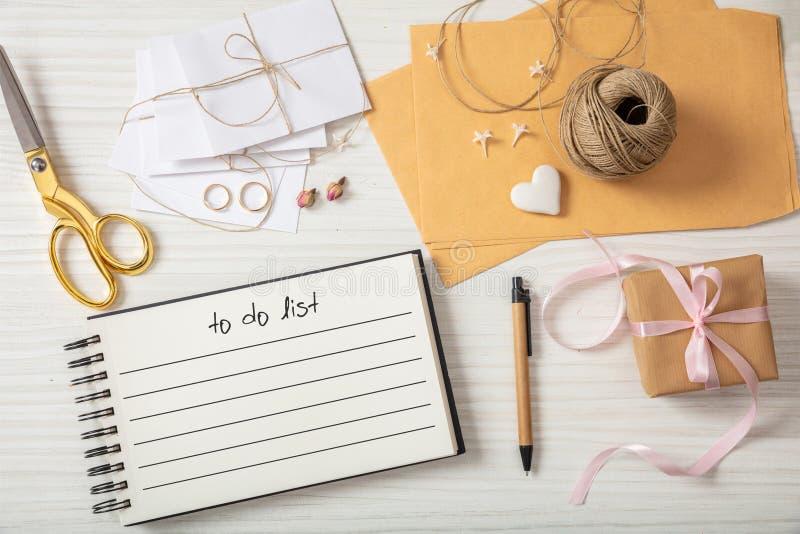 Flache Lage und Draufsicht von zu-listen und Hochzeitseinladungen auf einer weißen hölzernen Tischplatte, Leerstelle auf stockfotografie