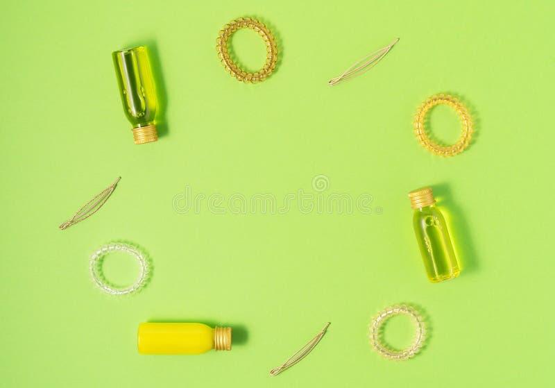 Flache Lage von Haarpflegeprodukten und von anreden Einzelteilen auf grünem Hintergrund Frauen Schönheit und Schönheitssalonkosme lizenzfreies stockfoto