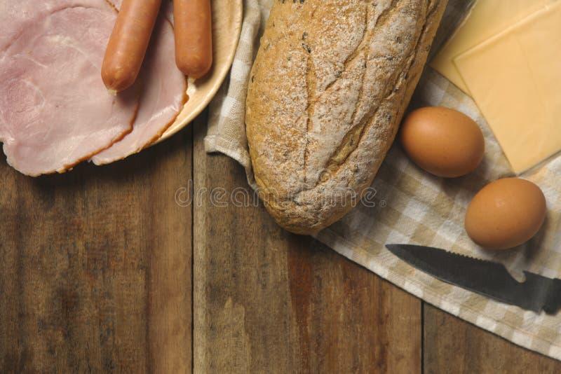 Flache Lage von verschiedenen Bestandteilen zum Frühstück auf hölzernem Hintergrund, Brot, Ei, Wurst, Schinken und Käse stockfoto