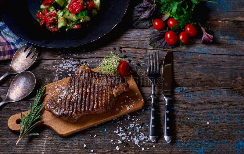 Flache Schärfentiefe Stück Grilled BBQ-Rindfleisch mariniert in den Gewürzen und in den Kräutern auf einem rustikalen hölzernen B lizenzfreies stockfoto