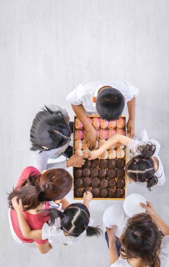 Flacher gelegter Schuss der Asiatin und asiatische Kinder heben nette Schalenkuchen vom Kasten auf stockbilder