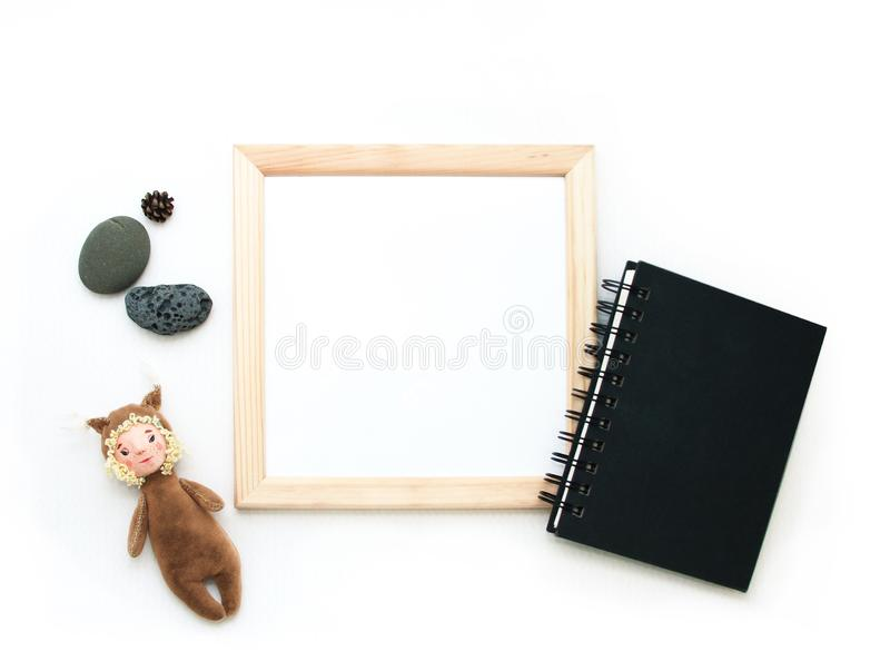 Flacher gelegter Spott oben, Draufsicht, Holzrahmen, Spielzeugeichhörnchen, Steine, schwarzer Notizblock Innenplan, quadratische stockfotografie