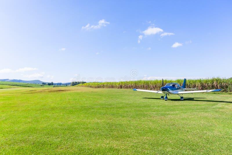 Flacher heller Stützen-Flugzeug-Bauernhof-Gras-Startstreifen stockfotos