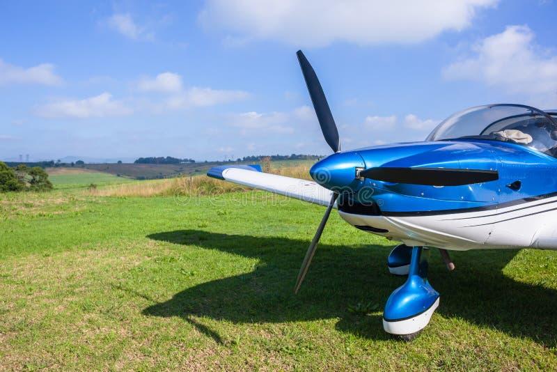 Flacher heller Stützen-Flugzeug-Nahaufnahme-Bauernhof-Gras-Startstreifen lizenzfreie stockfotografie