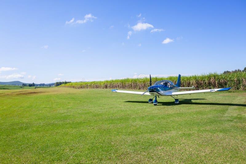 Flacher heller St?tzen-Flugzeug-Bauernhof-Gras-Startstreifen lizenzfreie stockbilder