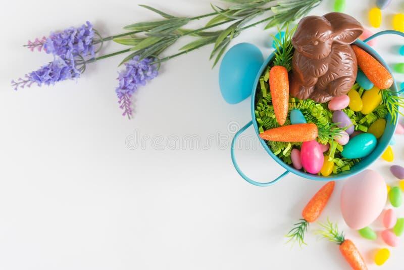 Flacher Lage Ostern-Hintergrund mit Minikarotten, Lavendel, Ostereiern und Schokoladenhäschen lizenzfreie stockfotos